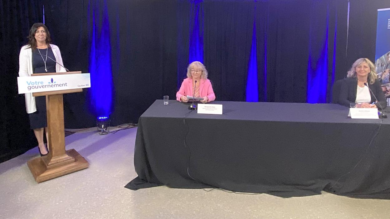 Une femme à un lutrin et deux autres à une table noire.