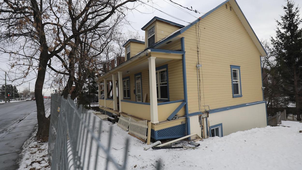Une maison jaune et bleue, avec une petite galerie en avant, et des clôtures de construction, sur un terrain enneigé.