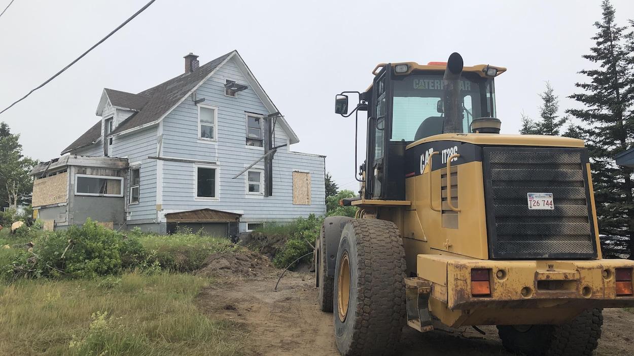 La maison en piteux état. Devant elle, un camion de construction effectue des travaux.