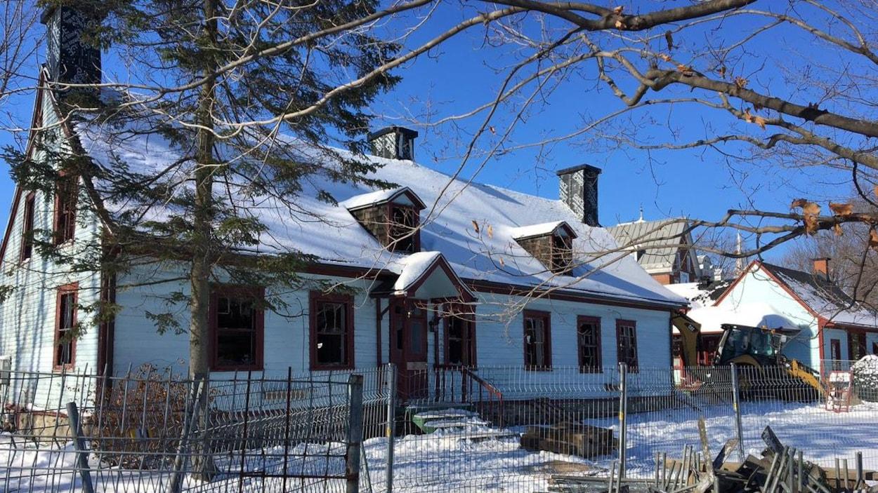 La maison est ceinturée d'une clôture de métal.