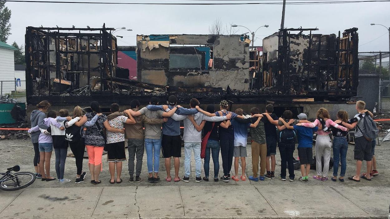 Des jeunes s'enlacent en guise de solidarité devant les restes d'un bâtiment brûlé.