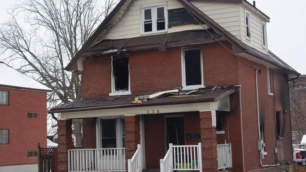 Photo du domicile en briques rouges noircies à l'arrière par les flammes.