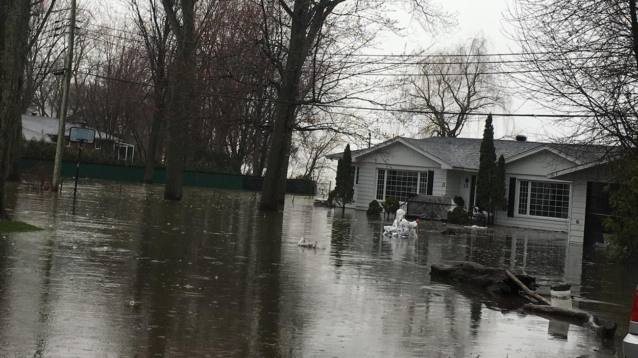 Une maison unifamiliale vue de l'extérieur avec tout son terrain inondé.
