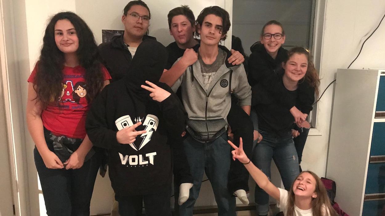 Des adolescents posent pour la caméra, certains riant, d'autres faisant des signes de paix.
