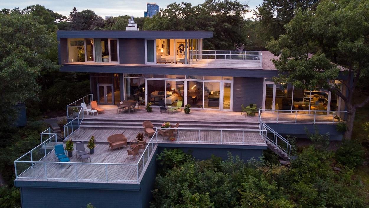 Photo d'une maison contemporaine à deux étages, beaucoup de fenêtres et une grande aire de vie à l'extérieur.
