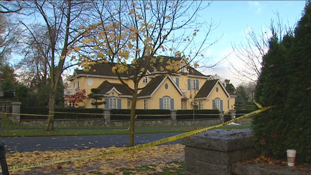 Un ruban jaune de la police interdit l'accès à un terrain entouré d'arbres au centre duquel il y a une imposante maison.