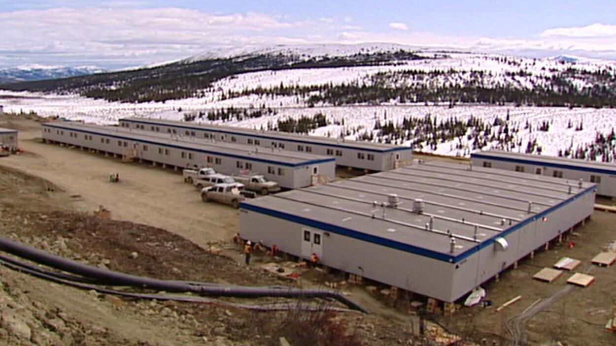 Des maisons mobiles de la mine Wolverine au Yukon vues depuis le sommet d'une colline avec au loin des arbres sous la neige.