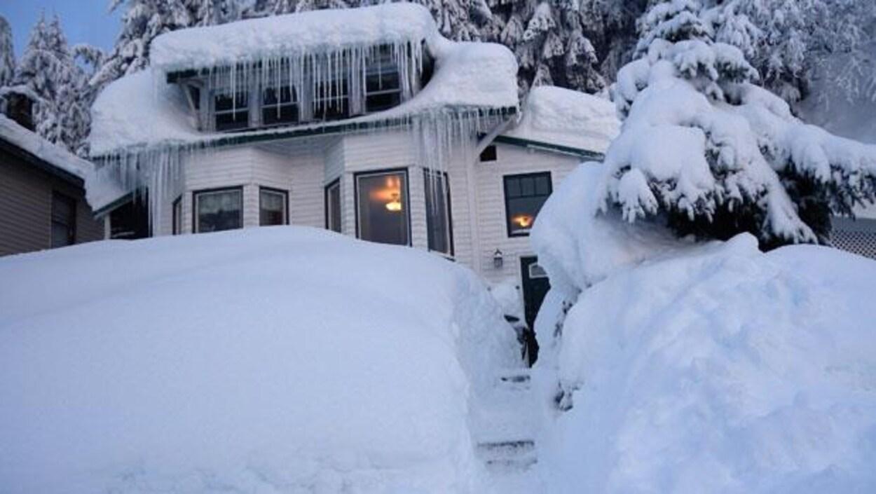 Une maison résidentielle en bois entourée d'une immense quantité de neige.