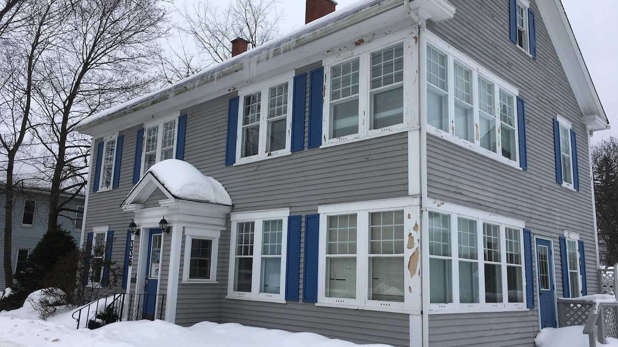 Une maison grise de deux étages avec de multiple fenêtres et à la peinture décrépite