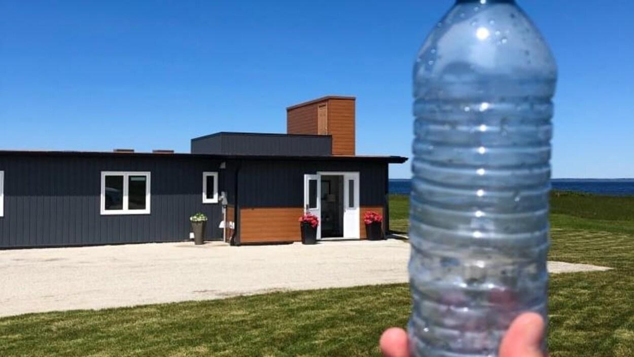 Image de la maison en plastique recyclé, avec une bouteille de plastique à l'avant-plan.