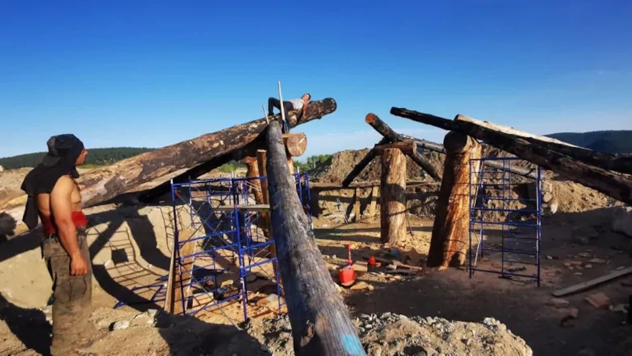 Deux personnes travaillent sur une maison semie-souterraine dont la structure est entourrée d'échafauds.