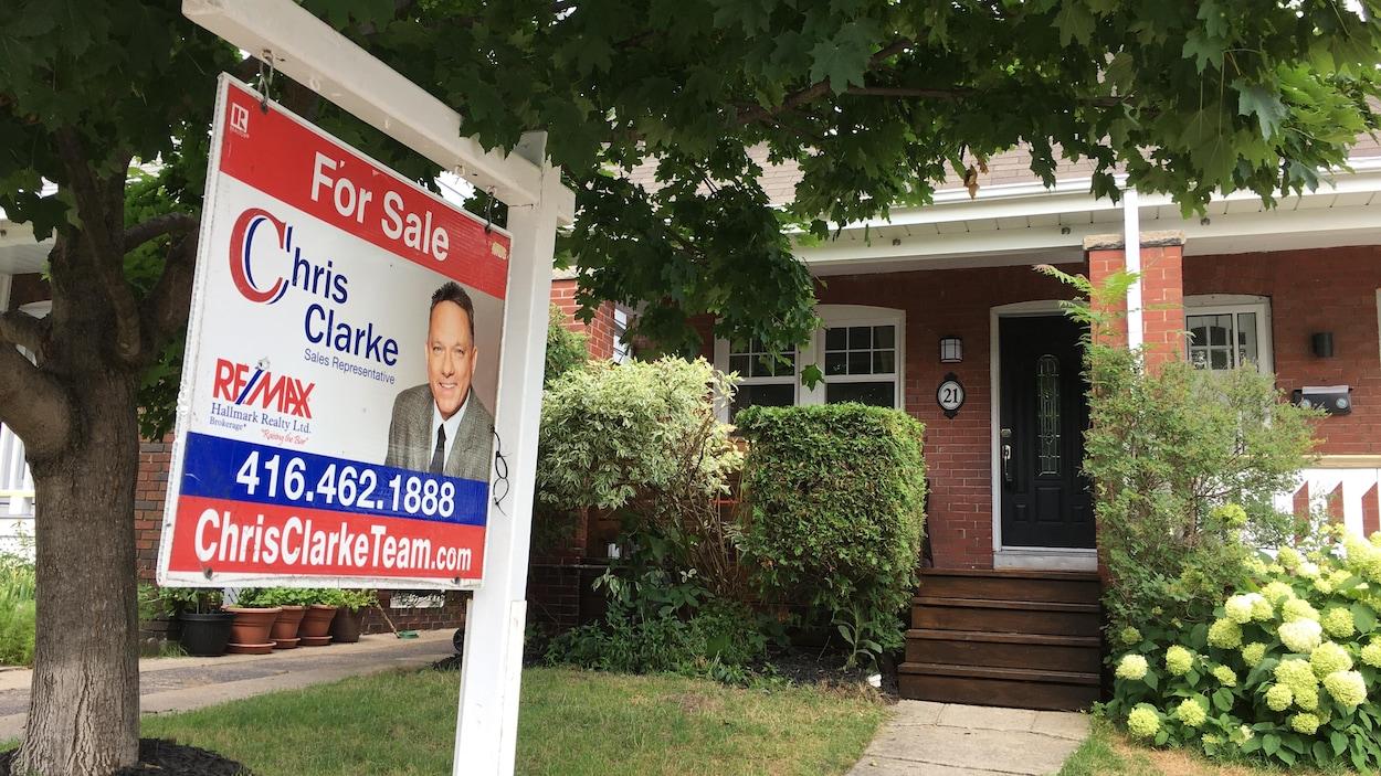 Une affiche de maison à vendre devant une demeure.