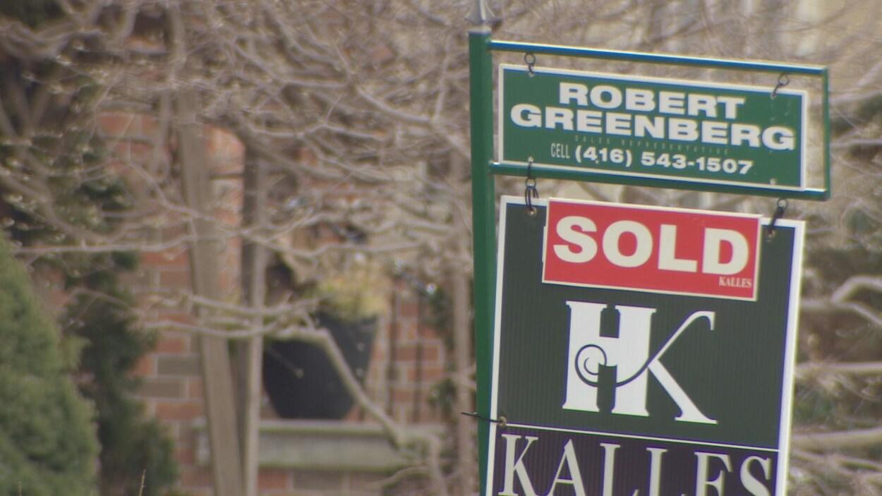 Affiche avec la mention « vendue » devant une maison