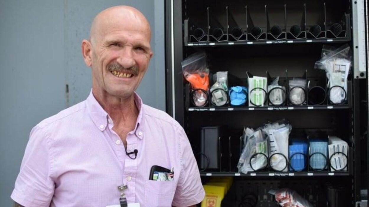 Malcolm McNeil debout près de la distributrice de seringues.