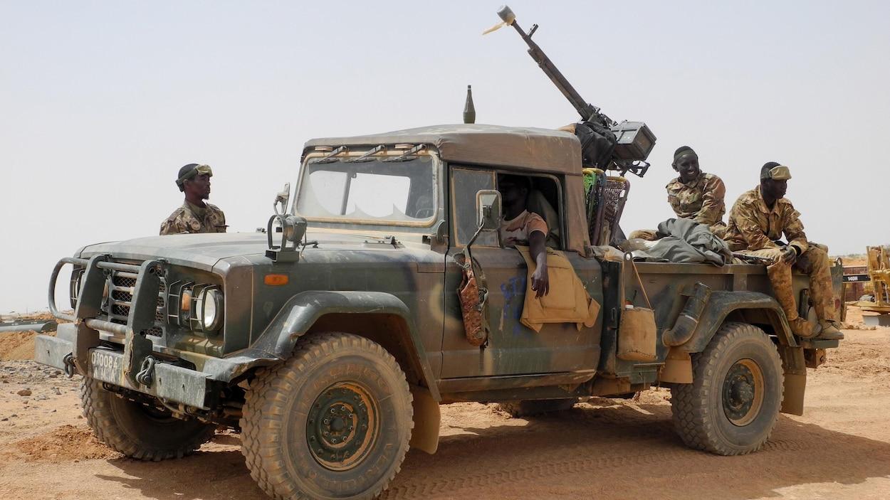 Quatre soldats près d'un camion-mitrailleuse de l'armée