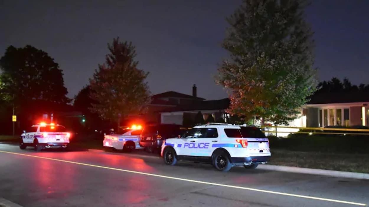 Photo de trois véhicules de police le soir garés devant une résidence dans une rue; leurs gyrophares sont allumés.