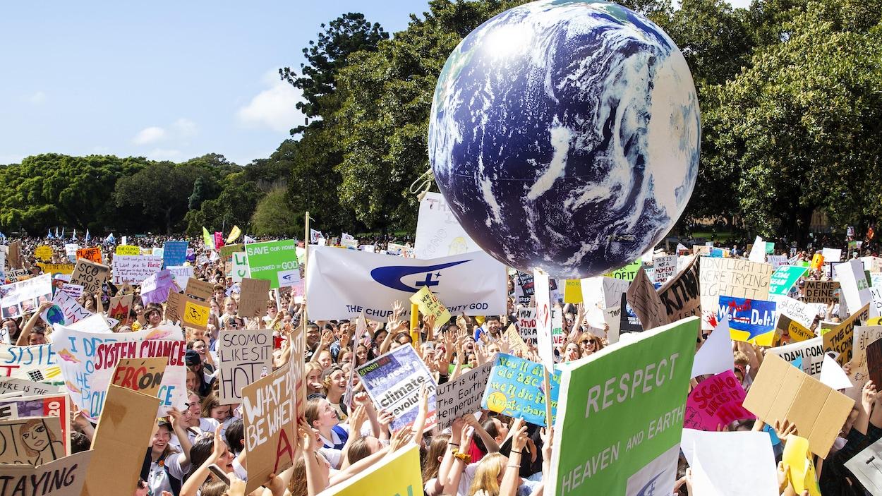 Des centaines de manifestants, en Australie, tiennent toutes sortes d'affiches et un grand ballon représentant la Terre.