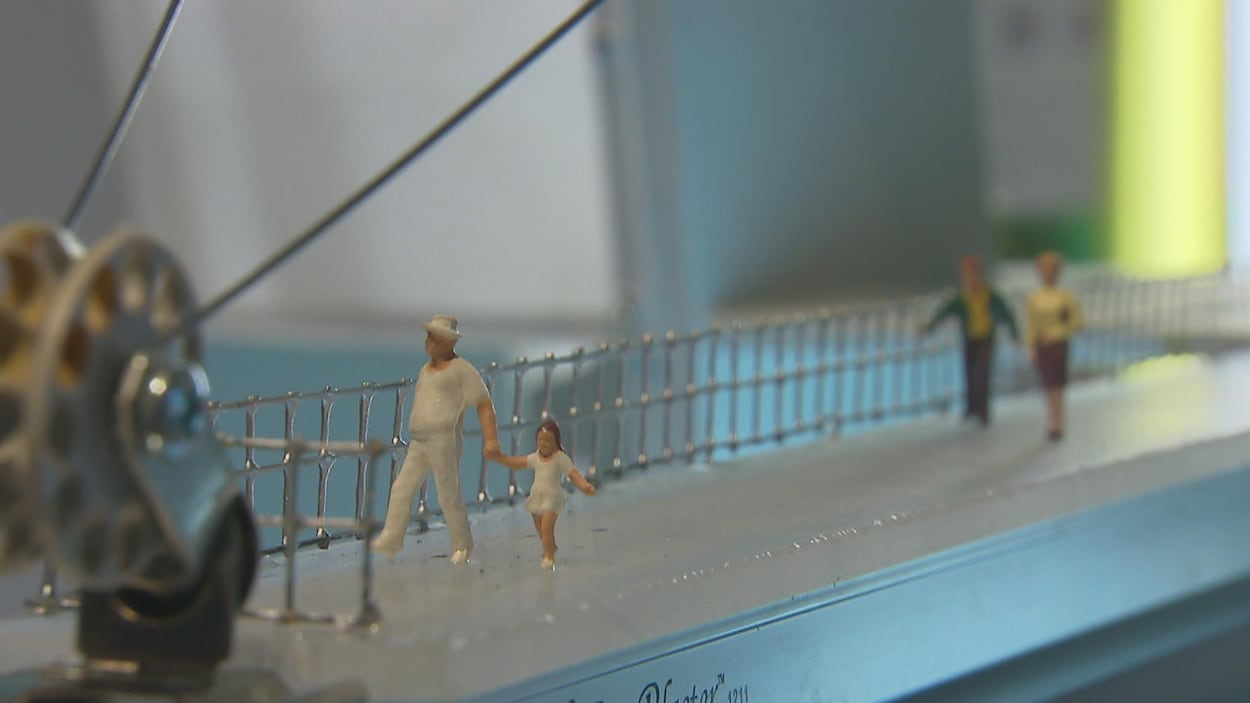 Petits personnages sur une passerelle surmontée d'une poulie