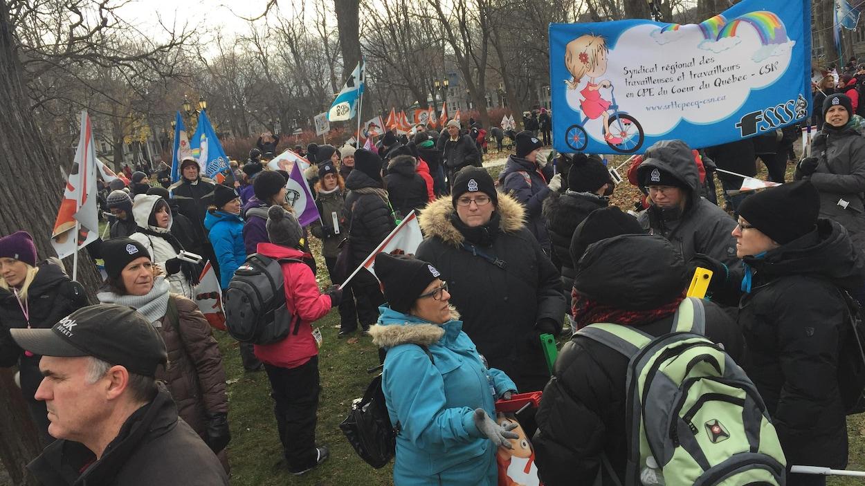Plusieurs personnes tenant des pancartes et des drapeaux se sont rassemblées au square Saint-Louis, à Montréal, pour demander un réinvestissement dans le réseau des CPE.