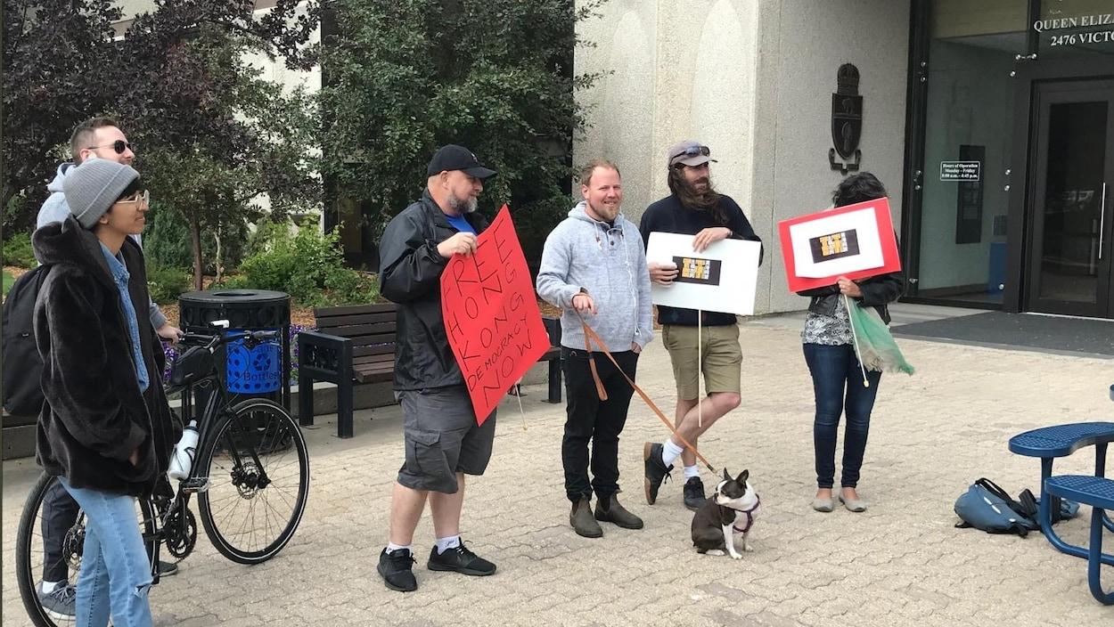 Six personnes tiennent des pancartes Free Hong Kong Democracy devant l'hôtel de ville de Regina.