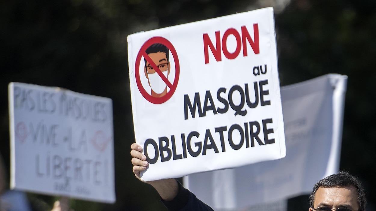 Une foule de personnes, sans masque, manifeste. Un homme tient une pancarte où l'on peut lire : Non au masque obligatoire.
