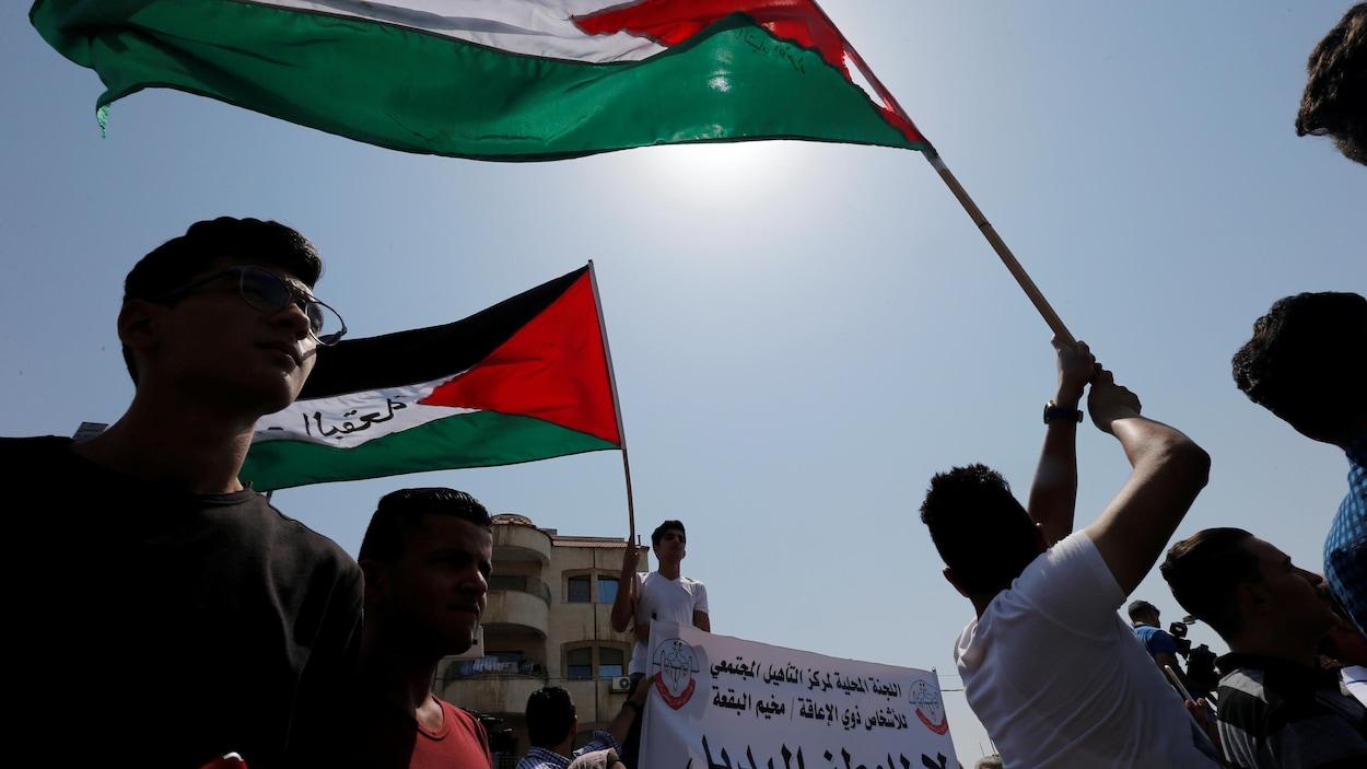 Des réfugiés palestiniens brandissent le drapeau palestinien lors d'une manifestation dans la capitale jordanienne, Amman.