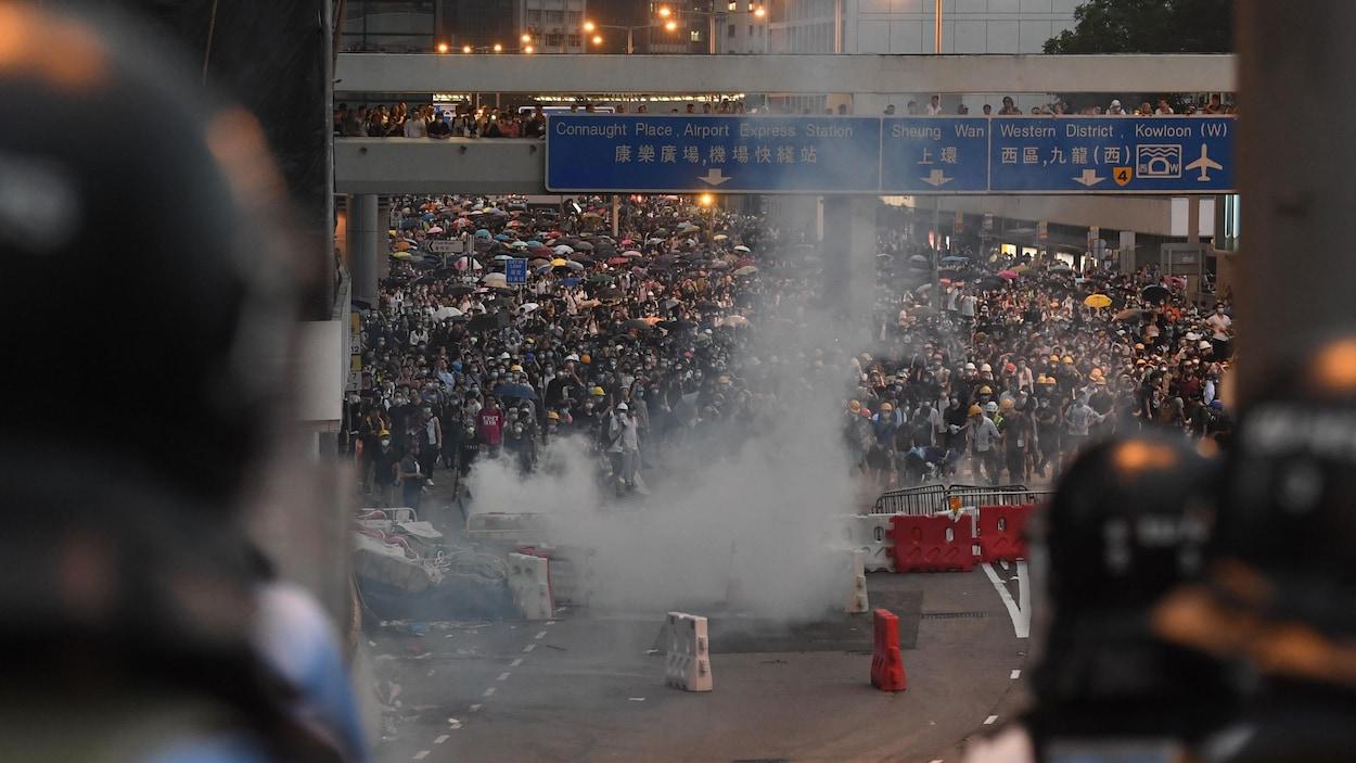 Une foule de manifestants baignés de fumée est vue entre les têtes de policiers en tenue anti-émeute.