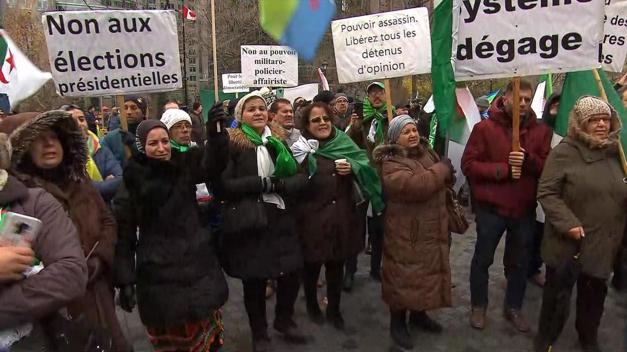 Les manifestants portent drapeaux algériens et pancartes.