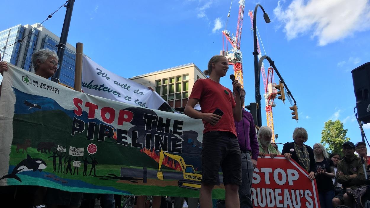 Un jeune tient un micro avec des manifestants derrière lui