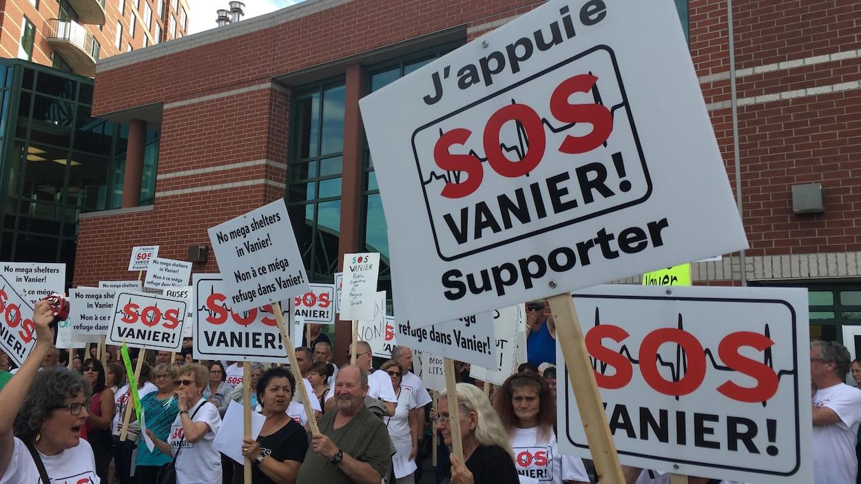 Des gens tiennent des pancartes affichant le message suivant : «J'appuie SOS Vanier supporter».