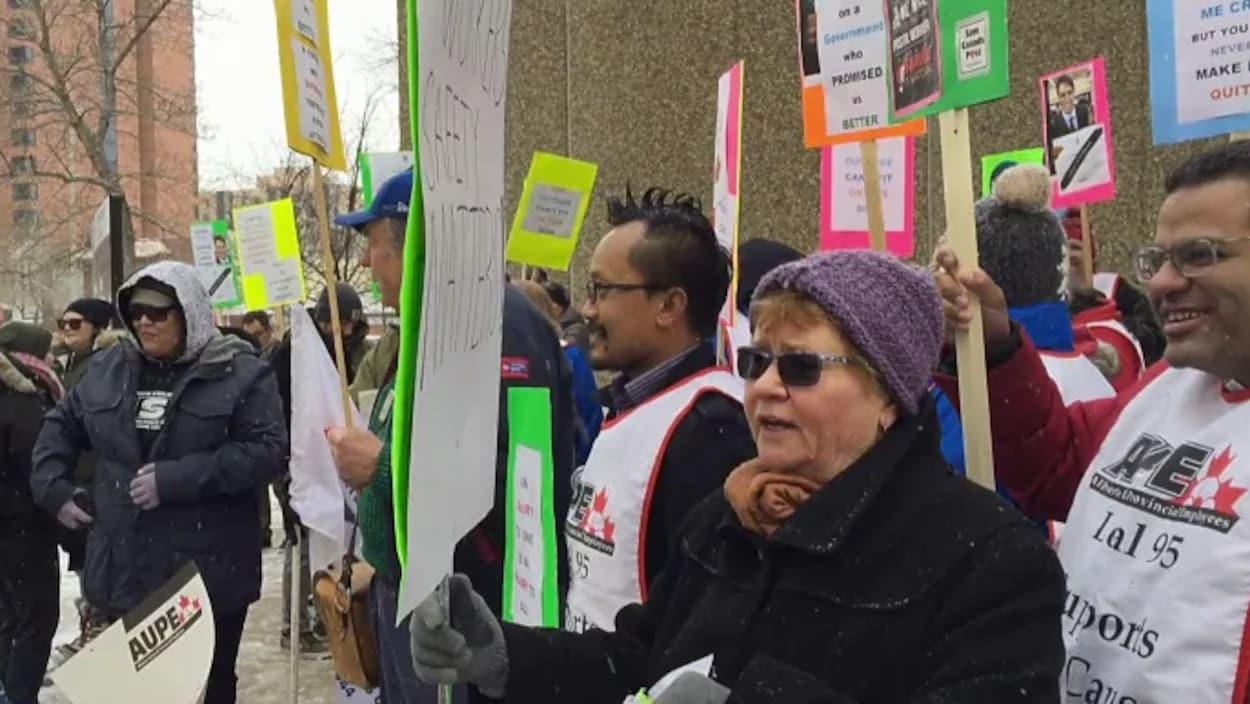 Des dizaines de manifestants à Calgary brandissent des pancartes qui dénoncent le retour au travail forcé des employés de Postes Canada