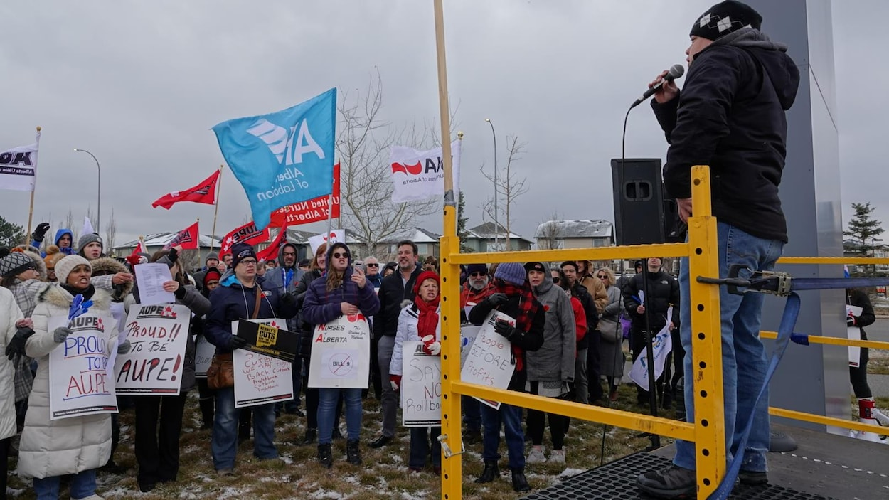 Une personne parle au micro devant les manifestants.