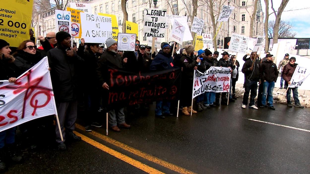 Des manifestants sont immobilisés sur la Grande Allée, devant l'hôtel du Parlement, à Québec. Plusieurs brandissent des affiches invitant le gouvernement Legault à renoncer à son projet de loi visant à déréglementer l'industrie du taxi.