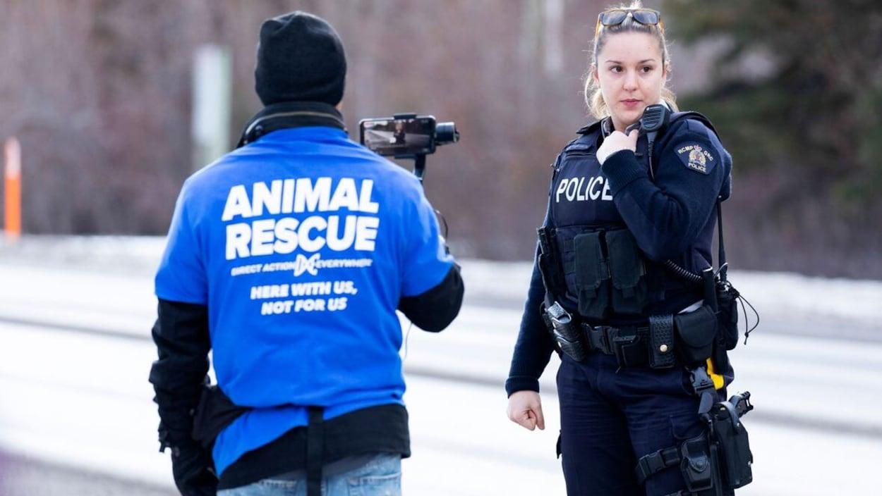 Une policière se tient debout près d'un manifestant avec un chandail qui dit Animal Rescue.
