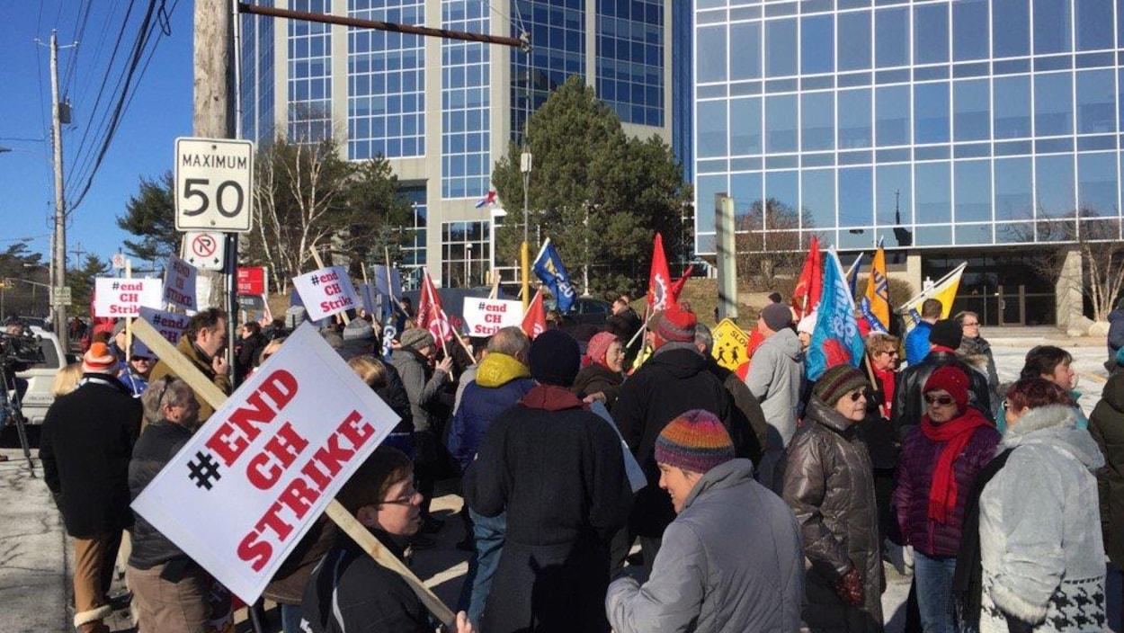 Des manifestants brandissent des pancartes devant les locaux du Chronicle Herald, à Halifax.