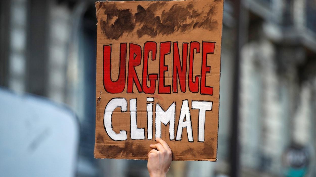 Une personne tient une pancarte sur laquelle on peut lire : « Urgence climat ».