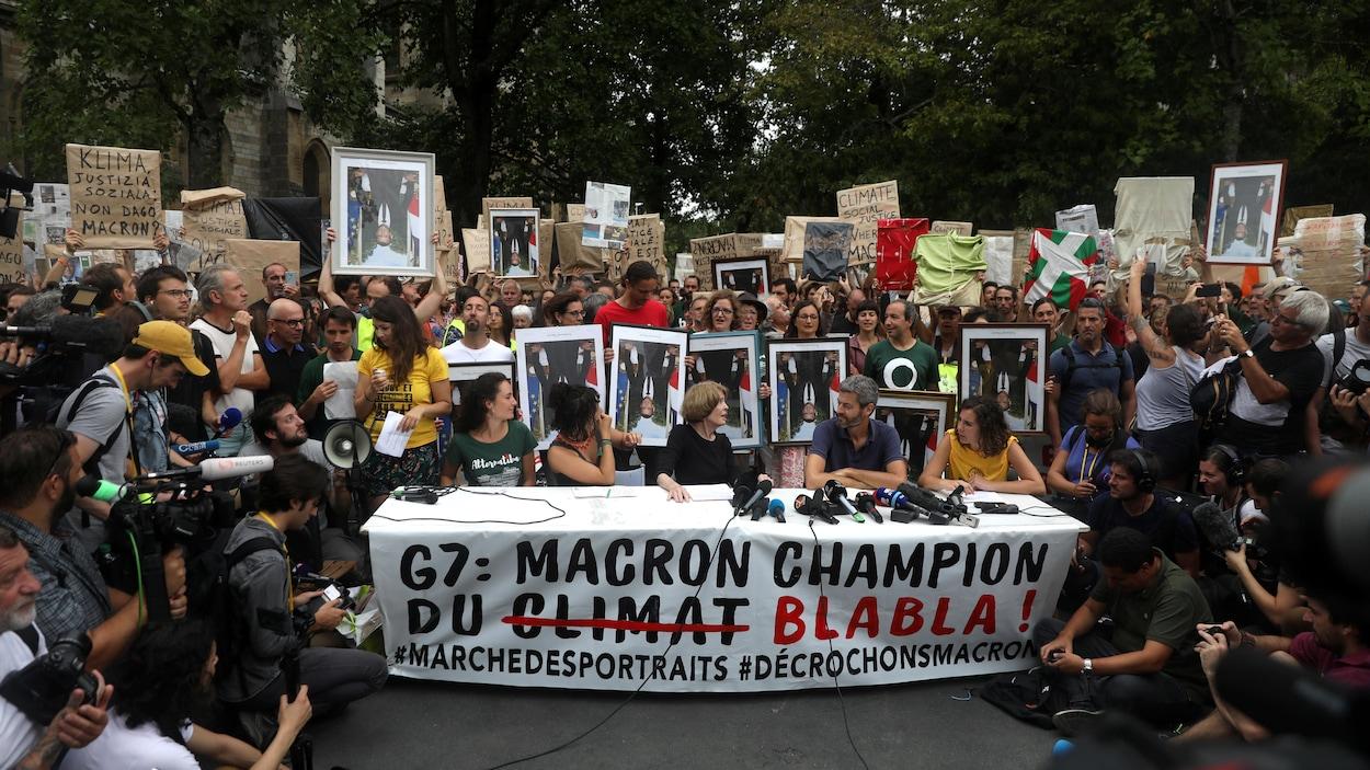 Des représentants d'ONG donnent une conférence de presse entourée d'une foule qui porte des portraits d'Emmanuel Macron à l'envers.