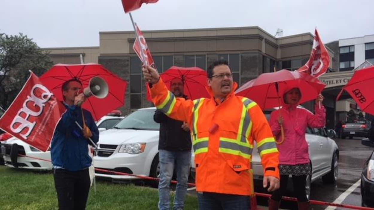 Des membres du SPGQ manifestent avec des drapeaux.
