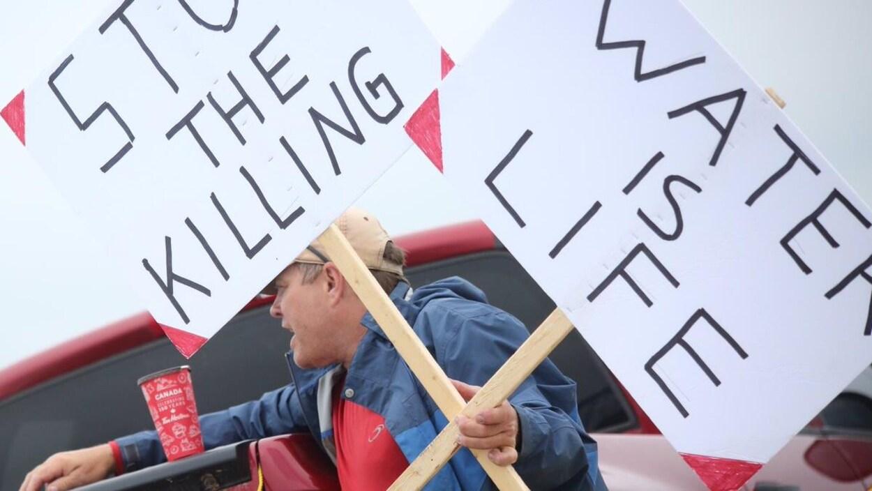 Un homme porte des pancartes pendant une manifestastion