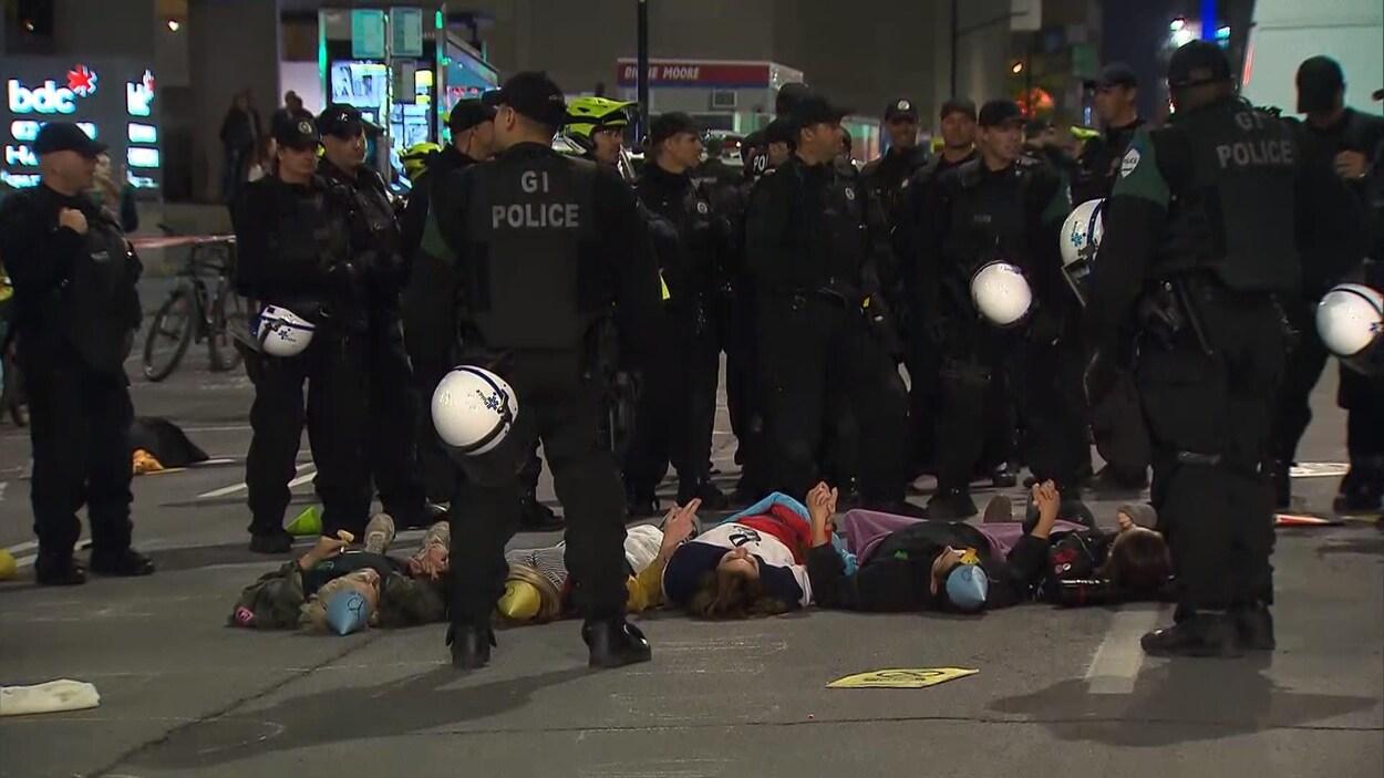 Des manifestants sont couchés au sol et entourés de policiers.