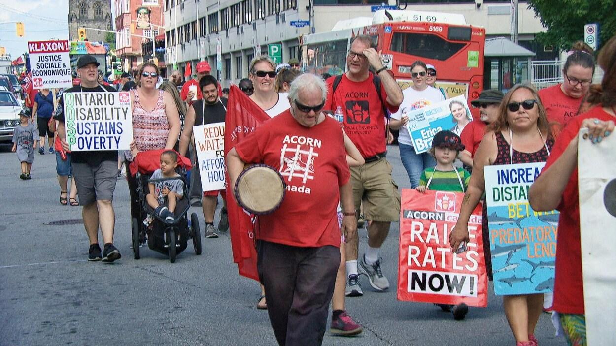 Des gens marchent dans les rues d'Ottawa avec des pancartes.