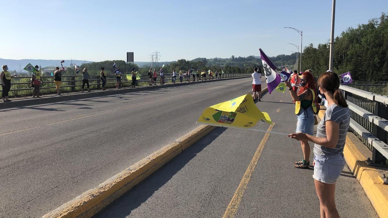 Des éducatrices se tiennent chaque côté du pont avec des drapeaux.