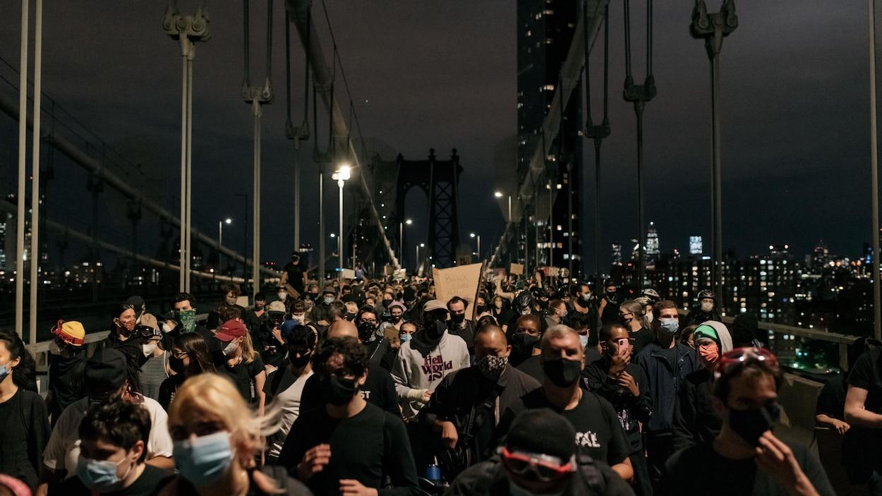 Des manifestants marchent sur le pont de Manhattan, à New York, en pleine nuit.
