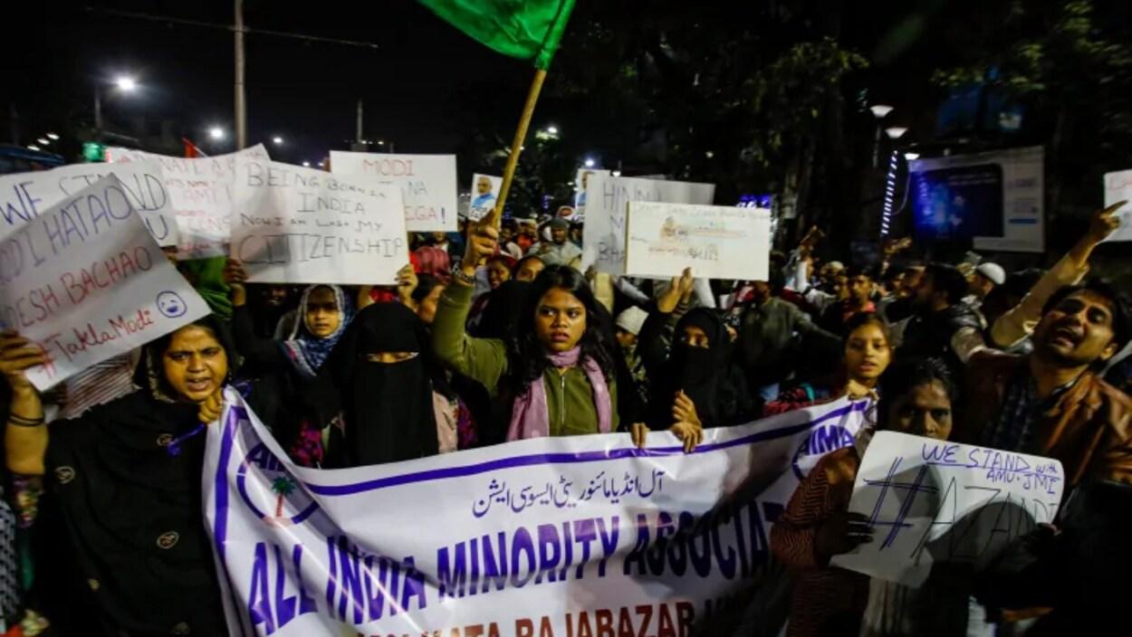Des Indiens crient des slogans lors d'une manifestation, la nuit.