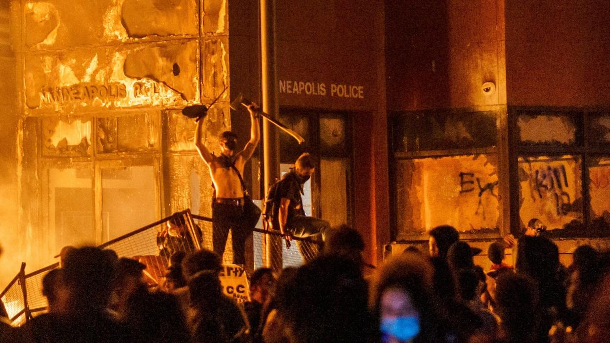 Des manifestants sont debout sur une barricade devant un poste de police qui a été incendié.