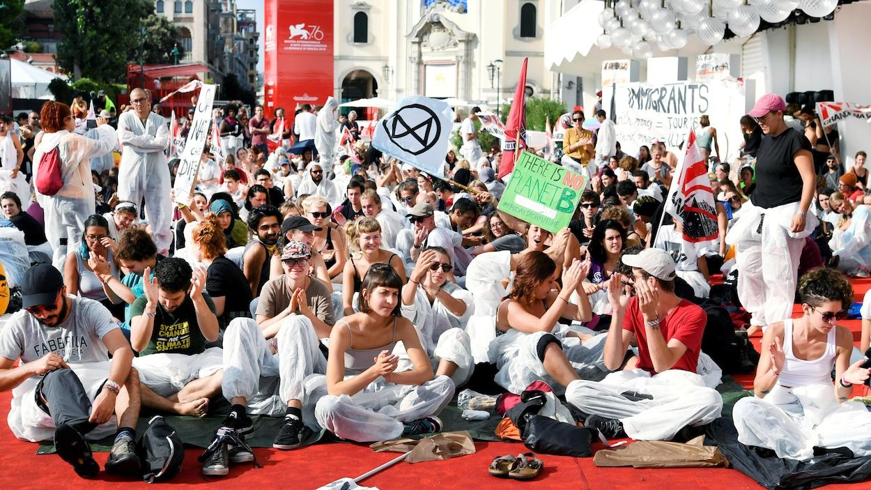 Des centaines de personnes sont assises sur le tapis rouge, avec banderoles et pancartes.