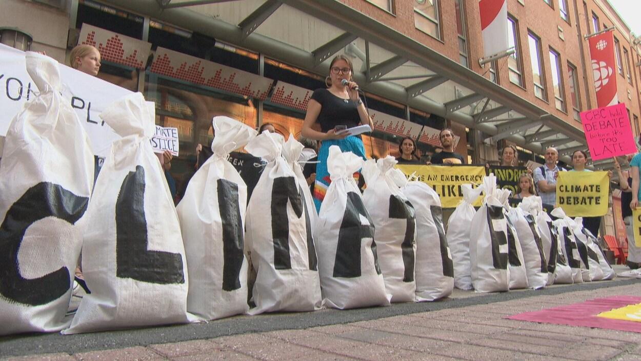 Des manifestants se tiennent derrière de gros sacs sur lesquels sont apposées des lettres écrivant le mot « Climat ».