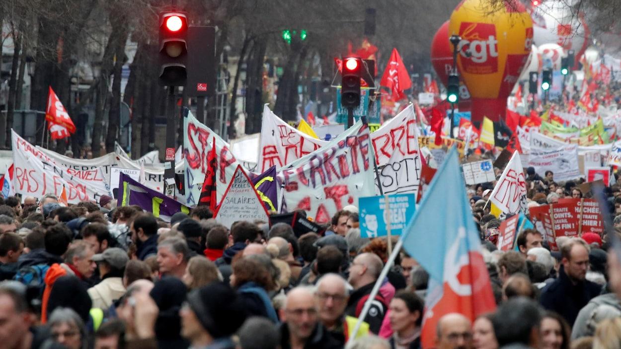 Des centaines de personnes marchent dans une rue de Paris. On voit de multiples banderoles.