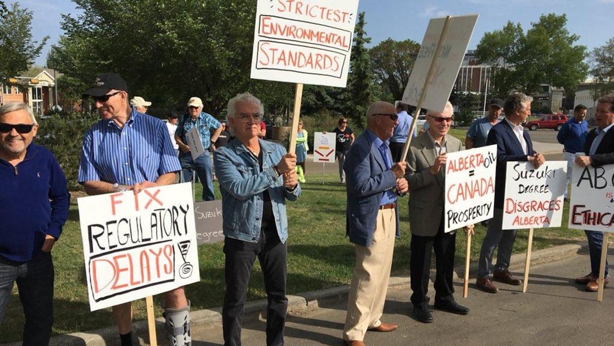 Une demi-douzaine d'hommes brandissent des pancartes avec des slogans qui supportent l'industrie pétrolière albertaine.