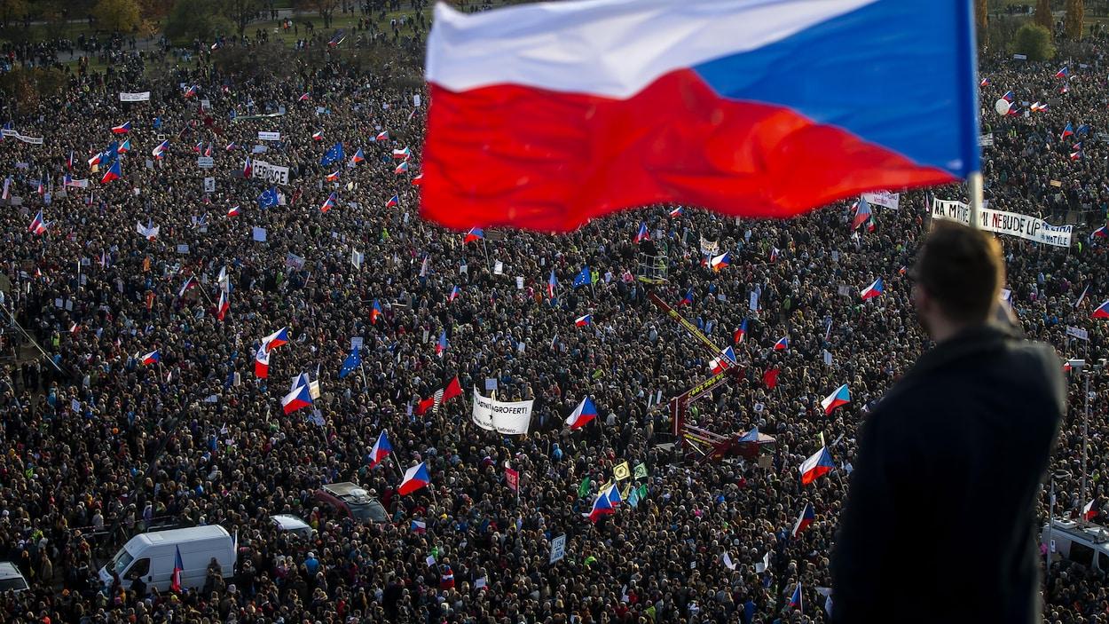 Un homme de dos tient un drapeau tchèque devant une foule de plusieurs dizaines de milliers de manifestants, à Prague, le 16 novembre 2019.